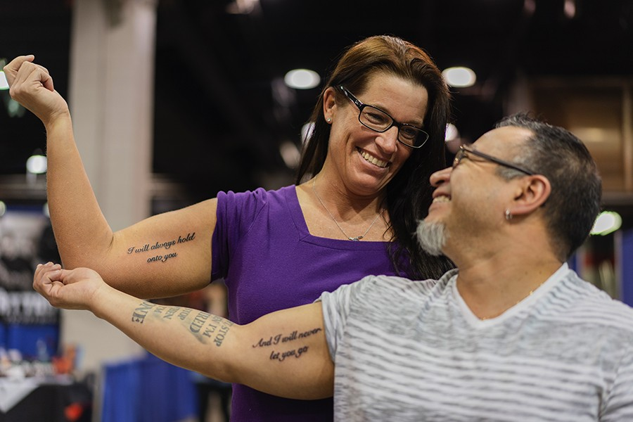 """Andy Siordia, 47, and Mindy Albert, 46, proudly display their complementary tattoos, which Siordia says they got on their arms because Albert holds onto his arm when they sleep. """"It's the way that we feel [about each other],"""" he says. - PAT NABONG"""