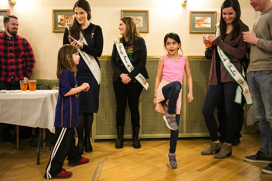 Aine McNulty dances to Irish music next to her mother, Deirdre (to her left), while the O'Hara School of Irish Dancers performs around the corner at the Irish American Heritage Center's Annual Lenten Fish Fry. - BRITTANY SOWACKE