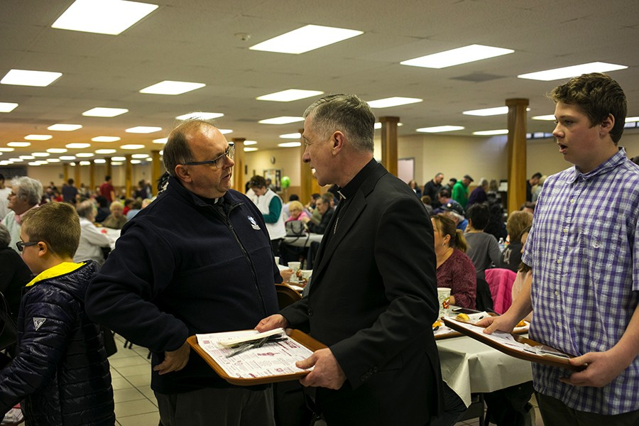 Illinois Cardinal Blase J. Cupich, center, made his first appearance at Saint Albert The Great Catholic Church in Burbank, IL on Friday, March 29, 2019. Cardinal Cupich speaks with Pastor Mariusz Nawalaniec, left, as her waits in line for fish dinner with parishioners. - BRITTANY SOWACKE