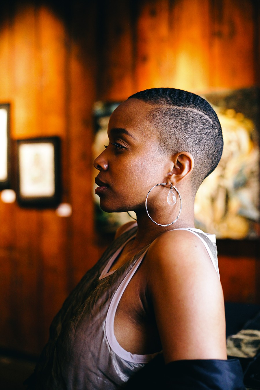 """Jamila Woods in the Dr. Margaret Burroughs Gallery, named after the SSCAC cofounder who also helped open the DuSable Museum of African American History in 1961. The gallery currently hosts the group exhibit """"Flowers in the Garden: A Tribute to the Struggles and Triumphs of the Black Woman."""" - LAWRENCE AGYEI"""