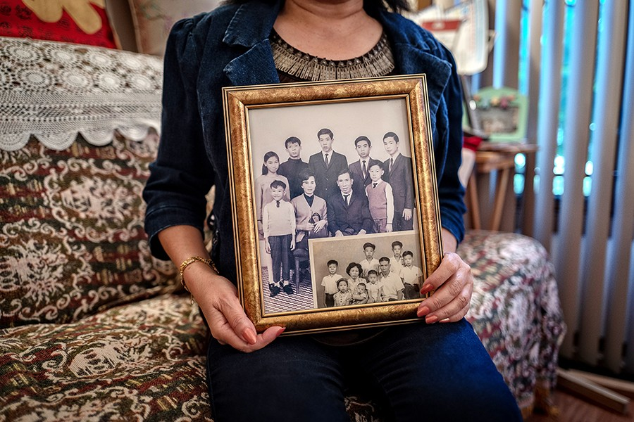 "She proudly holds a photo of her family back in Hong Kong. ""They were very expensive,"" she says of the studio portraits. ""But my mother made sure we got them done."" - HILLARY JOHNSON FOR CHICAGO READER"