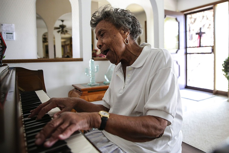 "Mama Lou belts out the hymn ""Pass Me Not, O Gentle Savior"" on the piano in her home. ""These old fingers don't play so well anymore,"" she says. - GEOFF STELLFOX FOR CHICAGO READER"