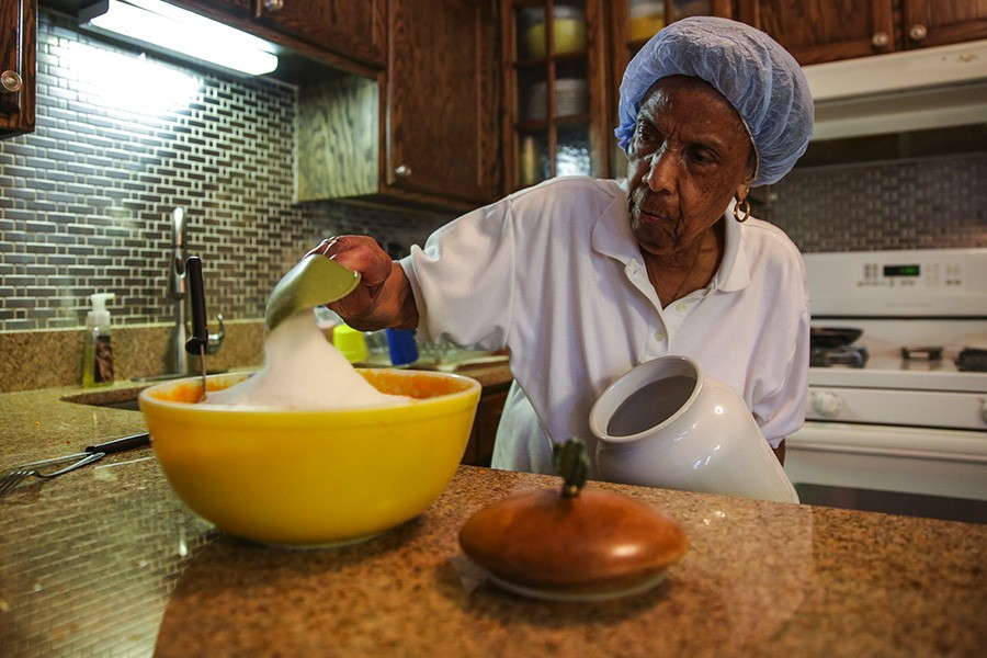 "Mama Lou is famous in the church community not just for her talent as a music director but also for her sweet potato pie. ""I don't measure,"" she says, scooping sugar in her kitchen. - GEOFF STELLFOX FOR CHICAGO READER"