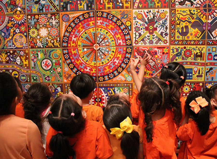 """Children at the """"Huichol"""" mural at the National Museum of Mexican Art, one of many museums that can afford to stay free thanks to census-related funding. - COURTESY NNMA"""