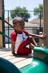 Two-and-a-half-year-old Noah in a playlot behind the Metropolitan Family Services office. Noah and his family receive home visits from the agency.
