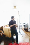 Scallon experiments with his new berimbau, one of three dozen musical instruments he owns.