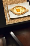 <i>Ajaruli khachapuri</i>, an  entree-size boat hollowed and filled with molten cheese, butter, and a raw egg yolk