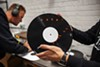Andy Weber of Smashed Plastic listens for imperfections in a test pressing while his colleague John Lombardo examines another copy by eye.