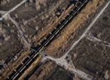 Terry Evans, Train loaded with petcoke moving through brown field, site of former steel mill, in Southeast Chicago, 2015 - TERRY EVANS