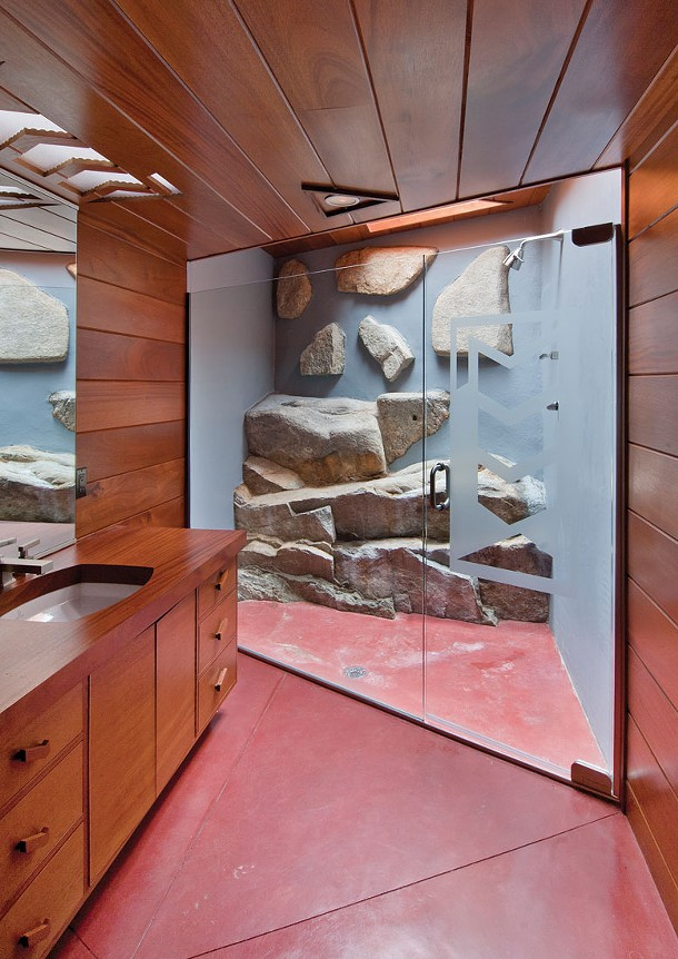 A guest bathroom with protruding boulders and skylight.