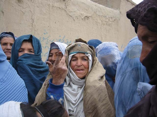 A woman outside an NGO office in Paghman, Afganistan, waiting in a long line to register for aid.
