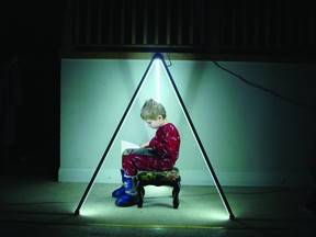 Andy Neal's son Miles sitting inside a pyramid of ILLUMATUBES powered by flashlight batteries. - MICHAEL SIBILIA