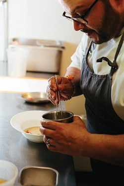 Chef Rei Peraza plating locally foraged ramps into a dish - THOMAS SMITH