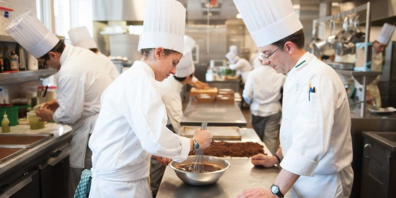 The Bocuse Restaurant Chef Stephane Weber (right) instructs Jay Gerardi (left) in a chocolate layered cake demonstration. Jennifer May