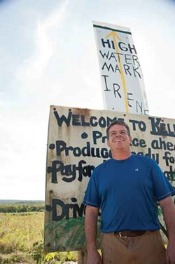 Chris Kelder standing in front of the sign indicating the high-water mark at Kelder's Farm in Accord. - ROY GUMPEL
