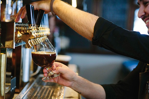 Christian Astorga pours a glass of house brewed beer - THOMAS SMITH