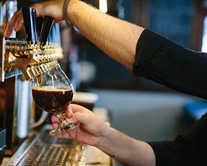 Christian Astorga pours a glass of house brewed beer