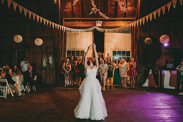 Claire throws her bouquet during her wedding reception at Tralee Farm in Stone Ridge. - LEV KUPERMAN PHOTOGRAPHY / LEVKUPERMAN.COM