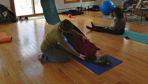 clyde forth adjusts a student in Pilates Community Class