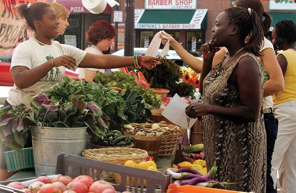 Customers shop for produce at the Food Project's Farmer's Market in the Boston neighborhood of Dorchester. According to James Howard Kunstler, as we head into our low-energy future, we will rely more and more on local food and local businesses.