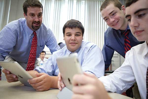 Gonzalo Garcia-Pedroso and students watch news clips as part of a discussion of current events at South Kent School. - DAVID SPAGNOLO