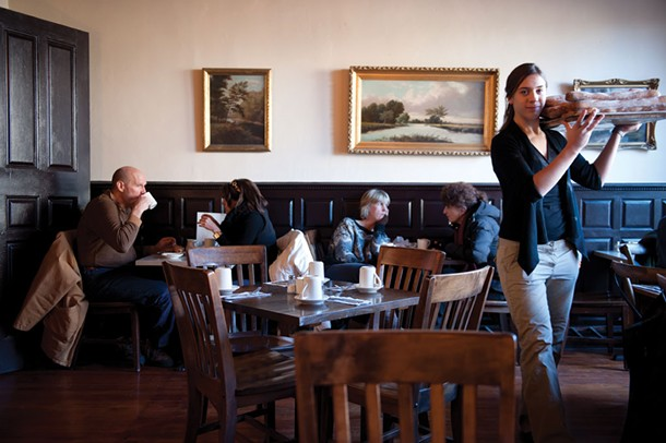 Hannah Otten carries freshly baked baguettes through the dining room at Café le Perche. - JENNIFER MAY