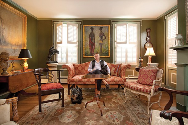 Haynes Llewellyn seated on a 19th-century Chinese Chippendale sofa in the living room with his rescue Scotties Mac and Heather. The walls are painted Gardenia Leaf Green, a color created by 20th-century designer Billy Baldwin. - DEBORAH DEGRAFFENREID