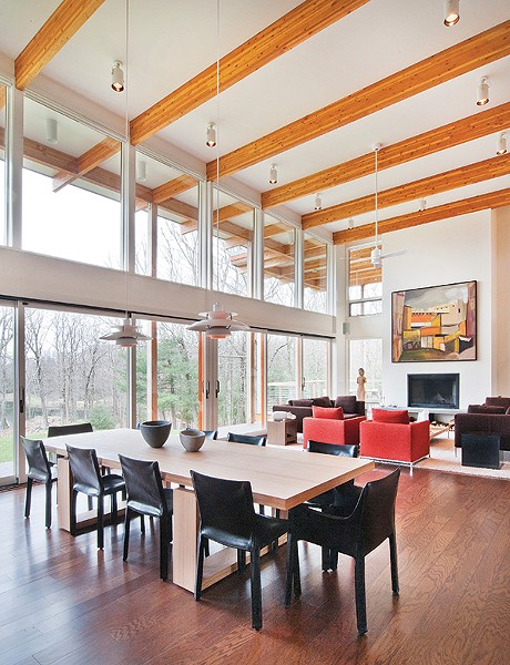 he dining area and great room's two-story walls of glass overlook the private pond. The post-and-beam construction emphasizes the strength of the home.