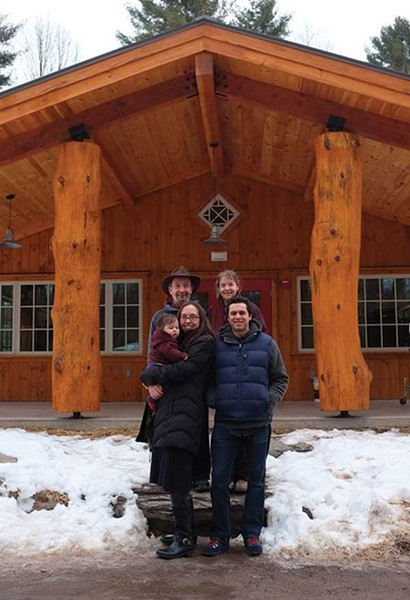 Jay Ungar, Molly Mason, Ruthy Ungar, Mike Merenda, and baby Opal Merenda in front of the dining hall at the new Ashokan Center in Olivebridge. - FIONN REILLY