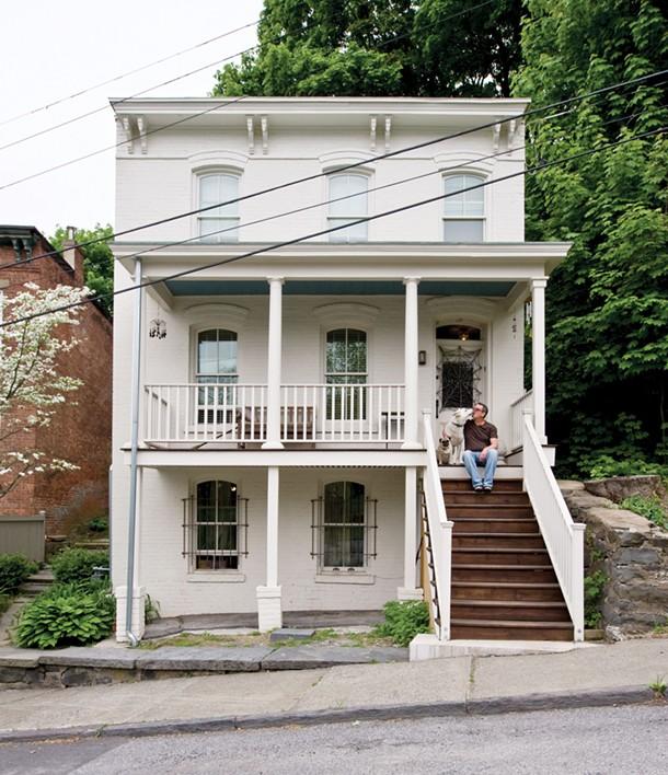 Jonathan Korn on the porch of his gutted and rebuilt home on Ravine Street in Kingston with his pug Jobim and shepherd Jazz. - DEBORAH DEGRAFFENREID