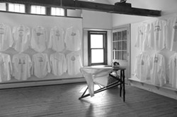 Kellner's most recent installation, Iron, looks at the history of women's domestic labor, printed screened photographs of antique irons, on the backs of crisp white shirts in invisible ink. The images are revealed by the heat of an electric iron, also part of the installation.