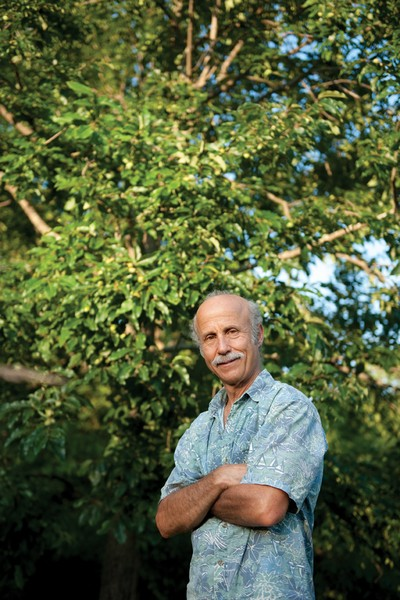 Lee Reich in front of a mature persimmon tree. The persimmon is highly recommended by Reich as part of an edible landscape. They yield 40 to 400 pounds of fruit, have few pests, and need little or no pruning. - JENNIFER MAY