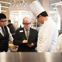The Bocuse Restaurant Manager in Training Robert Keller (center left) consults with Chef Robert Mullooly (center right) amidst lunch service. Jennifer May