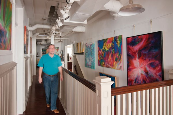 Morris in the central hallway, flanked by his paintings. - DEBORAH DEGRAFFENREID