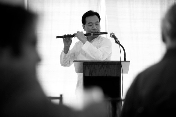 """Novelist and memoirist Da Chen serenades the crowd at the River of Words launch with a rendition of """"Danny Boy"""" on the Chinese flute. - JENNIFER MAY"""