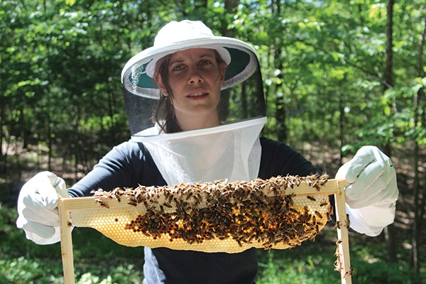Novice beekeeper Katie Benevento holds a frame from her hive. - PETER BARRETT