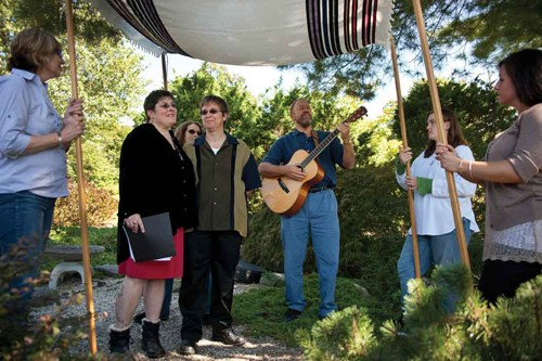 Peri and Tamela renewing their vows underneath the chuppa at Peace Park in New Paltz on September 18. Rabbi Jonathan Kligler plays the guitar while Cecilia Rainbow-Sloan (in white shirt) holds the chuppa.