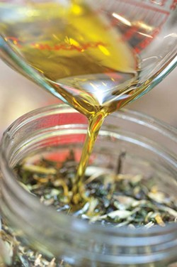 Pouring olive oil into an herb mixture.