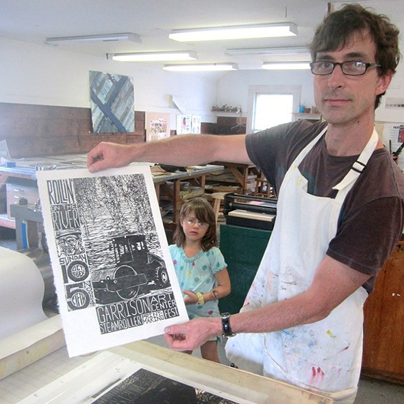Printmaker Jeff White creating woodblock print for Steamroller Printmaking poster (assisted by daughter). - CARINDA SWANN