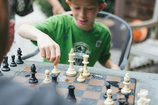 Sam Boergesson plays a game of chess at Water Street Market. - THOMAS SMITH