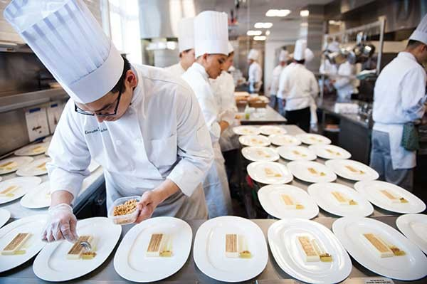 Students plate the cheesecake dessert course at lunch. - JENNIFER MAY