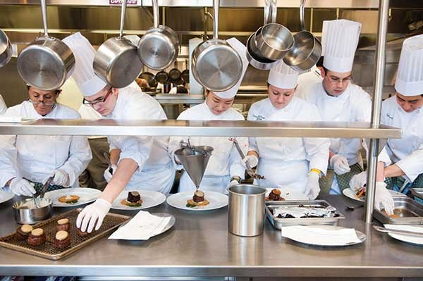Students prepare the fillet mignon entrée in assembly line fashion. - JENNIFER MAY