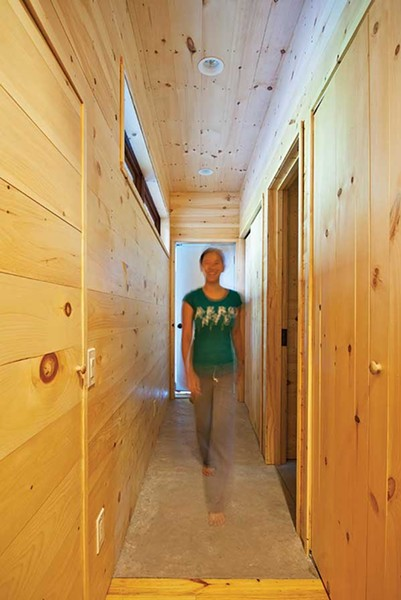 Suika Knowles in the narrow corridor connecting the bedroom and bathroom to the rest of the house.