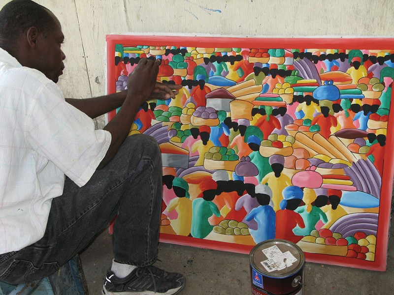 The artist Sonson putting the final touches on one of his works in Port-au-Prince.