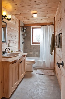 The bathroom tiles are cut limestone with visible embedded fossils. - DEBORAH DEGRAFFENREID