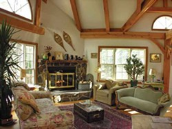 The Brandt's living room, furnished with personal treasures like the mantel over the fireplace (salvaged from a demo site in Manhattan), snowshoes from a former house in Canada, and a fireplace built with stones selected from the property. - PETER BRANDT