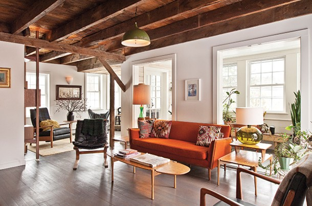 The living room features a sofa sourced from a Salvation Army store and - reupholstered with orange wool from the Pine Plains Firehouse feal market. - DEBORAH DEGRAFFENREID