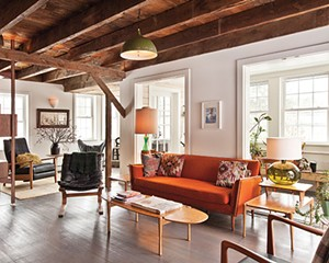 The living room features a sofa sourced from a Salvation Army store and  reupholstered with orange wool from the Pine Plains Firehouse feal market.