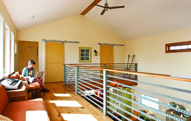The upstairs hallway has seven southern-facing windows to allow for passive solar heating. Industrial fans are used to push heat downstairs. Railings were made by Stahl and Redfern using wood and salvaged metal pieces. - DEBORAH DEGRAFFENREID