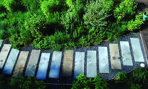 Densely planted herb garden with offset bluestone path. - LARRY DECKER